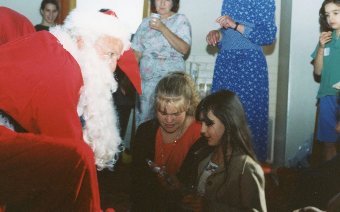 SMYLE Christmas Party December 1990. Albert James as Santa, Tutor Nicole Erickson, Rosamarina Morelli (child), Tutor Keren Shuvally, Home Visitor Margaret Cramer, (child-unknown).