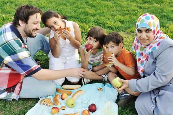 خانواده مسلمان ، مادر و پدر با سه فرزند با هم در طبیعت نشسته و روی چمن سبز غذا می خورند: پیک نیک